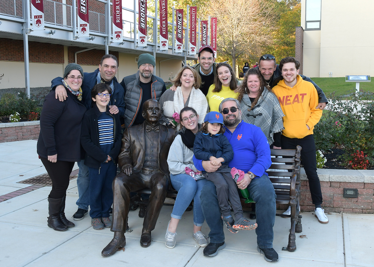Family poses with Rider statue.