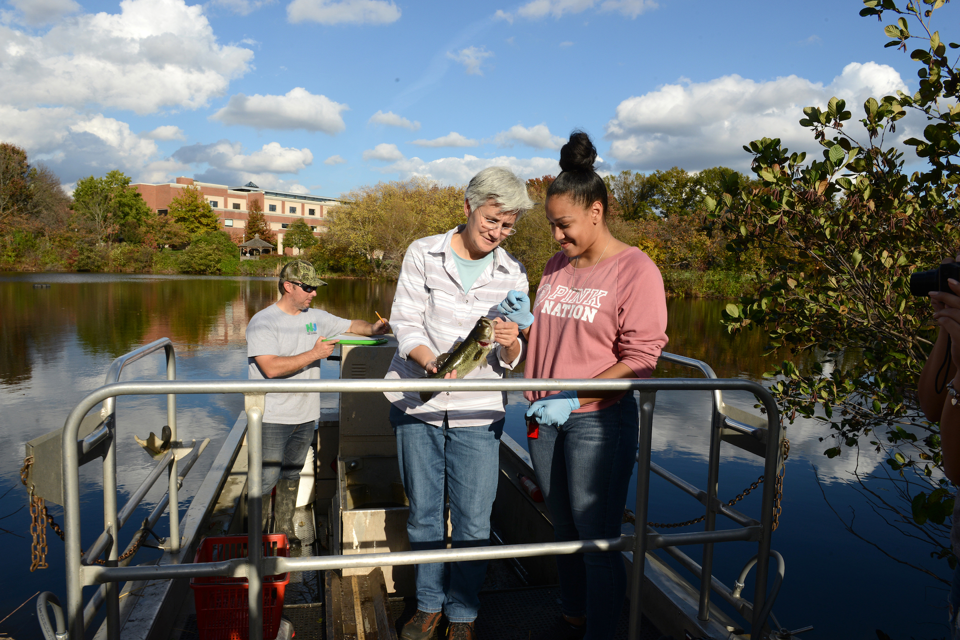 Student and faculty on a boat on Centennial Lake doing research